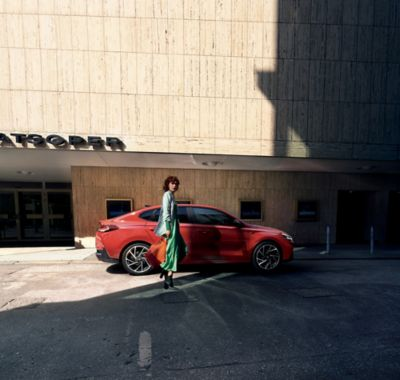 Femme élégante portant une robe verte et un sac de shopping rouge, se dirigeant vers sa nouvelle Hyundai i30 Fastback