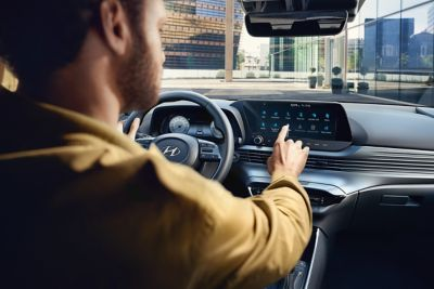 A man in the driver's seat operating the touchscreen of an all-new Hyundai i20