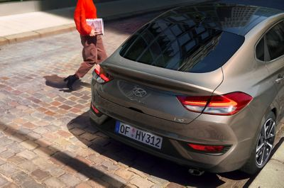 Woman approaching her new Hyundai i30 Fastback on the driver's side.