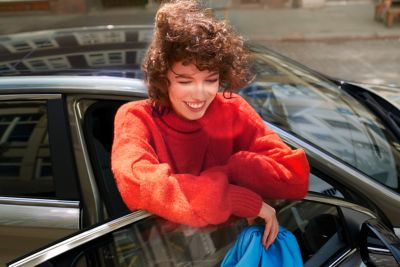 Woman in red sweater leaning on the passenger door of the new Hyundai i30.