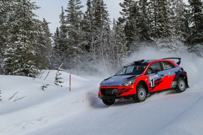 Hyundai Motorsport customer racing rally car i20 R5 drifting through a curve on a snowy road.