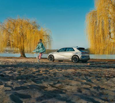 A person on a beach, approaching their Hyundai IONIQ 5 electric midsize CUV.