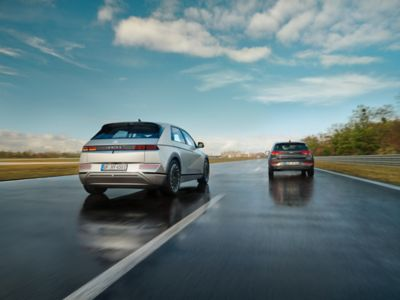 Hyundai IONIQ 5 electric midsize CUV travelling along a country road.