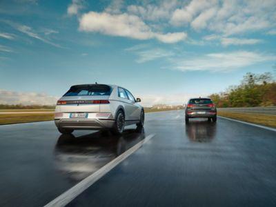 Un crossover 100% elettrico Hyundai IONIQ 5 che sorpassa un'altra auto su una strada di campagna