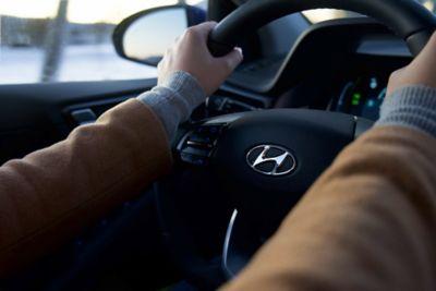 Mann med hendene på rattet i en Kona Electric. Foto.