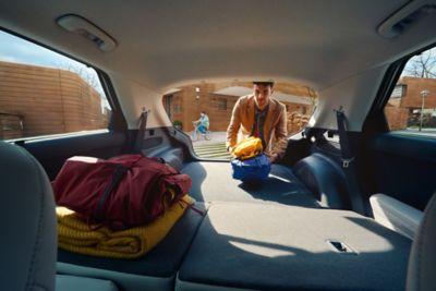 Un uomo carica il bagagliaio della sua Hyundai IONIQ 5 con i sedili posteriori ripiegati