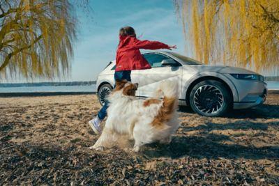 Bambino che gioca con un cane su una spiaggia con il crossover 100% elettrico Hyundai IONIQ 5 parcheggiato sotto alberi gialli