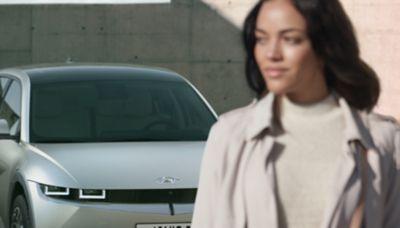 Una persona che si allontana dal suo crossover 100% elettrico Hyundai IONIQ 5 con il suo cofano a conchiglia