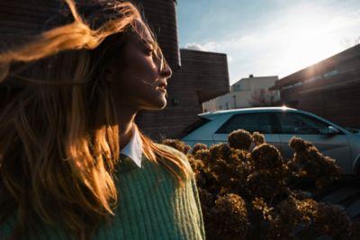 Un giovane che guarda lontano accanto al crossover 100% elettrico Hyundai IONIQ 5