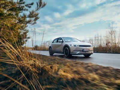 Hyundai IONIQ 5 kjører på en landevei. Foto.