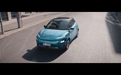Il SUV Nuova Hyundai Kona Electric alla guida su una strada della città.