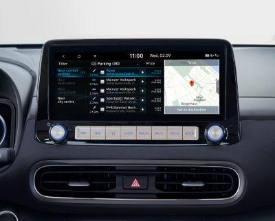 """Immagine dello schermo del sistema di navigazione da 10,25"""" di Nuova Hyundai Kona Electric che mostra informazioni sui parcheggi lungo la strada e in aree dedicate."""