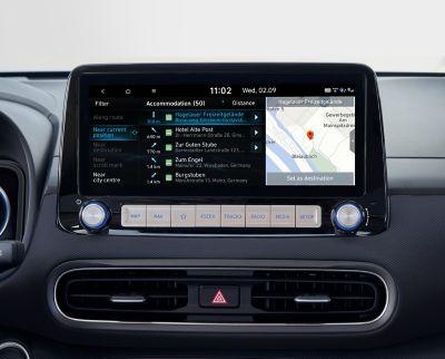 """Immagine dello schermo del sistema di navigazione da 10,25"""" di Nuova Hyundai Kona Electric che mostra punti di interesse in tempo reale."""