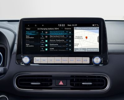 """Immagine dello schermo del sistema di navigazione da 10,25"""" di Nuova Hyundai Kona Electric che mostra informazioni sulle stazioni di ricarica."""