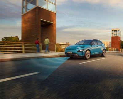 Nuova Hyundai Kona Electric con sistema Forward Collision-avoidance Assist al passaggio su un ponte.