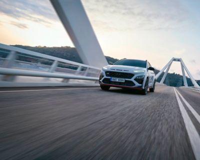 Nový Hyundai KONA N v barevném provedení Sonic Blue přejíždějící most, v pohledu zepředu.
