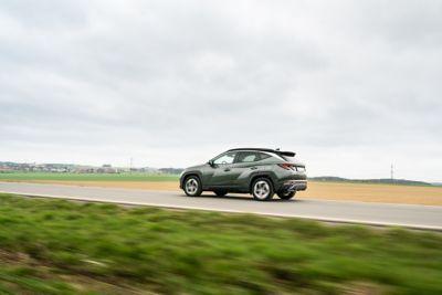 Boční pohled na Hyundai TUCSON Plug-in Hybrid, který jede na silnici vedoucí kolem pole.