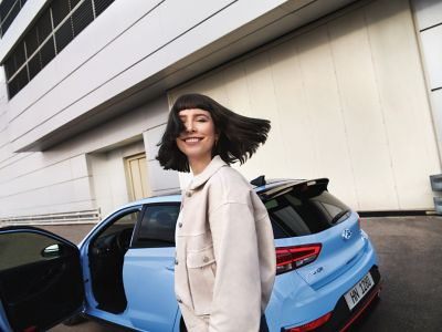 a young woman smiling as she gets ready to drive her new i30 N performance hatchback.