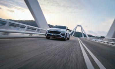 The all-new Hyundai KONA N in Sonic Blue going over a bridge.