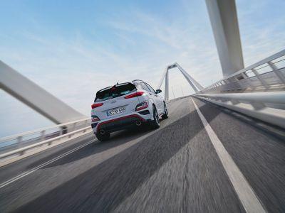 Vue arrière du SUV sportif Hyundai KONA N traversant un pont.