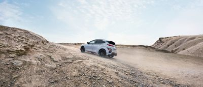Hyundai KONA N driving on an unpaved road in an open landscape