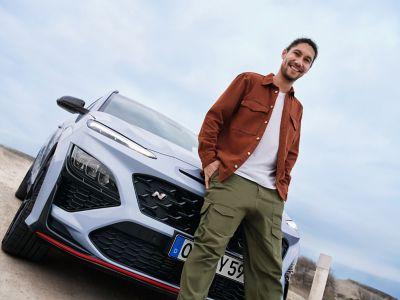 Un jeune homme adossé contre le capot du SUV sportif Hyundai KONA N, souriant avec assurance.
