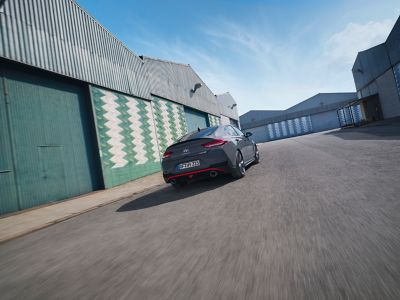 the new Hyundai i30 N Fastback driving in an industrial scenery from the rear.