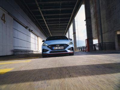 The new Hyundai i30 N from the front in Performance Blue colour driving along an industrial structure.