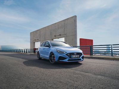 The new Hyundai i30 N from the front right in Performance Blue parked next to an industrial structure.