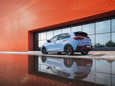 the i30 N performance hatchback from an angle, parked next to a reflective surface.