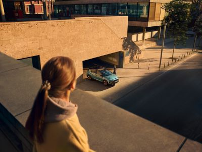 Topview of the all-new Hyundai BAYON compact crossover SUV driving out of a parking garage.