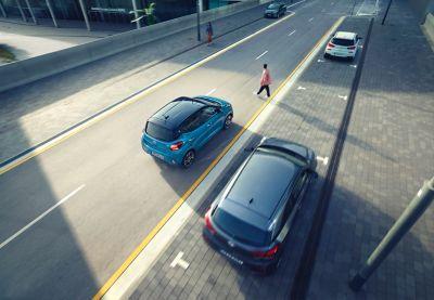 Véhicule Hyundai à l'arrêt devant un piéton traversant la rue.