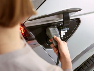 Ladestøpsel koblet til elbilen Hyundai IONIQ 5 crossover. Nærbilde.