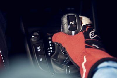 Main gantée d'un pilote de course saisissant le pommeau de levier de vitesses du SUV sportif Hyundai KONA N.