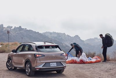 Two paragliders packing their chutes next to a Hyundai NEXO hydrogen fuel cell vehicle.