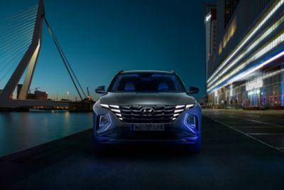 Hyundai Tucson Nowej Generacji jedzie nocą przez miasto, w tle most i oświetlone budynki.