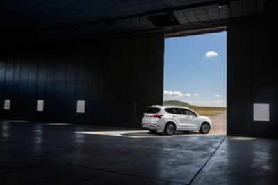 The new Hyundai Santa Fe SUV pictured from the side, parked in an airplane hangar.