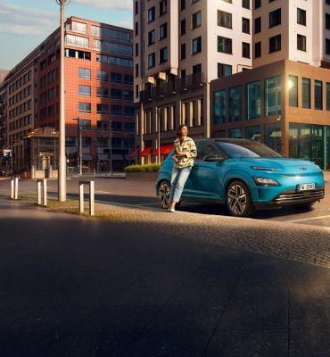 Una donna appoggiata a Nuova Hyundai Kona Electric in città.
