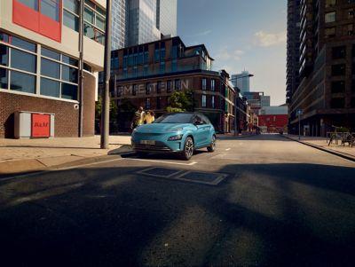 Immagine di Nuova KONA Electric parcheggiata lungo una strada di città con una coppia di ragazzi che le cammina a lato