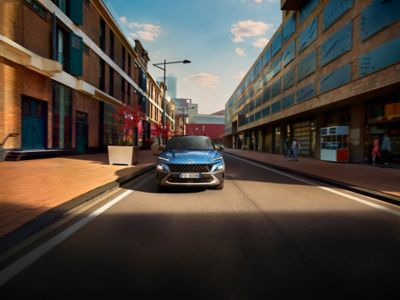 The new Hyundai Kona from the front in Surfy Blue driving through a busy city street.