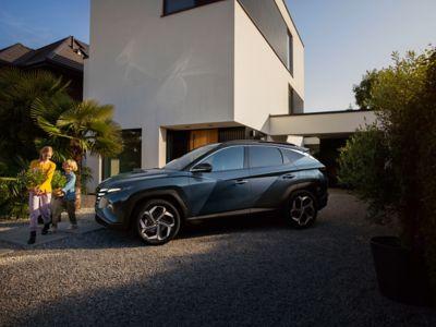 Immagine di Nuova TUCSON Hybrid parcheggiata di fronte a una casa con dei bambini che giocano a lato