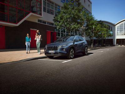 Immagine di Nuova TUCSON Hybrid parcheggiata lungo una strada di città con una famiglia che cammina a lato