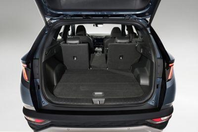 Il bagagliaio aperto del SUV compatto Nuova Hyundai TUCSON Hybrid con i sedili reclinati.