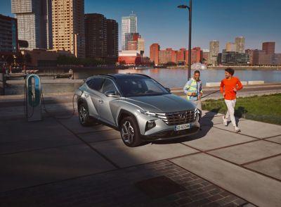 Immagine di Nuova TUCSON Plug-in Hybrid parcheggiata davanti a un corso d'acqua in città con due uomini che fanno jogging
