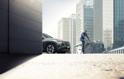 Immagine di Nuova TUCSON Hybrid che si immette in una strada e va verso ad un ciclista