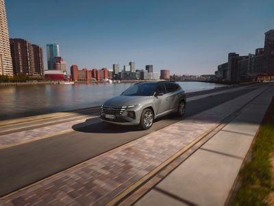 Vista anteriore di Nuova Hyundai TUCSON N Line in Shadow Grey che corre lungo un corso d'acqua in città.