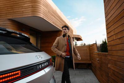 Un uomo in cappotto marrone che cammina intorno al crossover 100% elettrico Hyundai IONIQ 5
