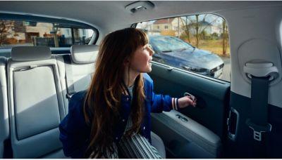 Un giovane che guarda fuori dal finestrino posteriore di Hyundai IONIQ 5