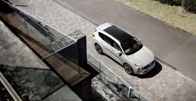 Vista dall'alto del SUV 7 posti Nuova SANTA FE bianco parcheggiato davanti a una casa.