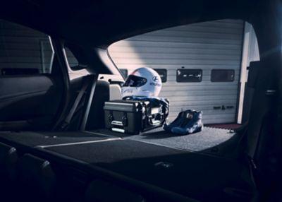 Casque, chaussures et équipement de course stockés dans le coffre du SUV sportif Hyundai KONA N.
